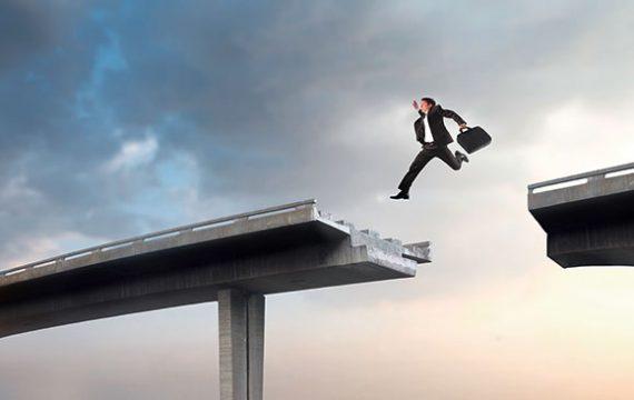 Mann in Anzug springt über Lücke in Brücke