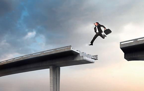 Mann springt mit Aktenkoffer über kaputte Brücke