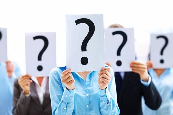 Personen mit Fragezeichen-Blättern vor den Köpfen