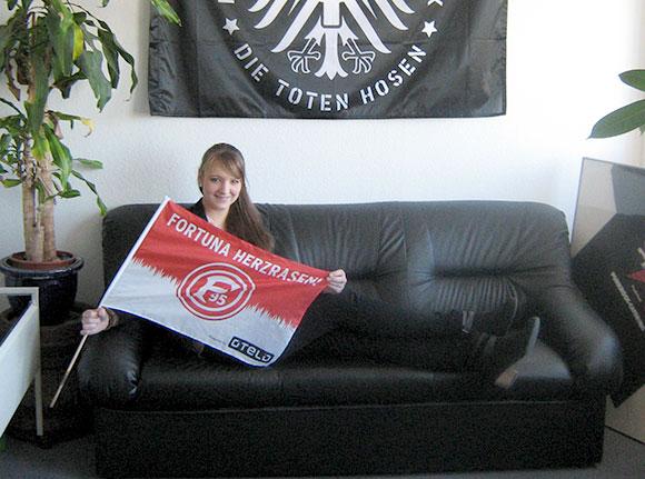 Frau mit Fortuna Herzrasen Flagge auf Sofa