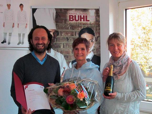 Frau Daniela Falkner (M.) erhält Blumen und Sekt von Eren Barlik (Regionalleiter) und Ina Radermacher (Personaldisponentin Service in Köln)