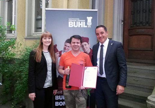 Ricarda Müller, Fachbereichsleiterin Service, und Regionalleiter Daniel Habibi-Naini (r.) gratulieren Herrn Sergey Borisov zum 5-jährigen BUHL-Jubiläum