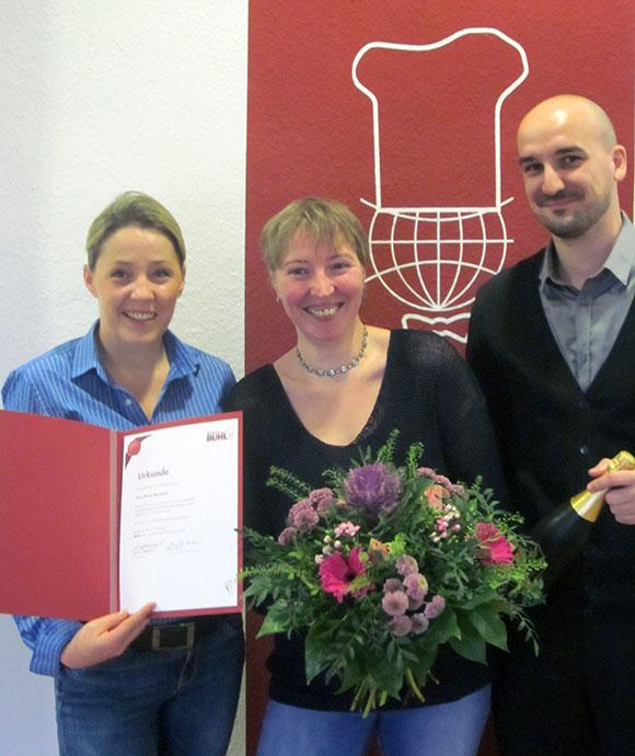 Mandy Blochwitz (Mitte). Jacqueline Schulz, Assistentin der Regionalleitung, und Dennis Grade, Personaldisponent Service, gratulieren mit Blumen, Sekt und BUHL-Urkunde