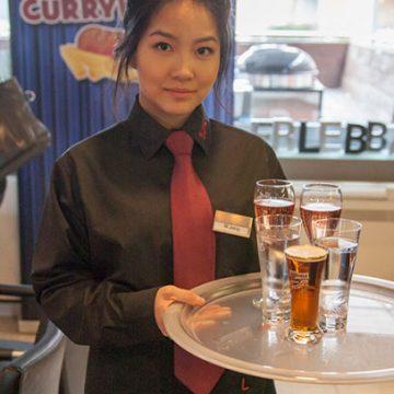 Kellnerin serviert Getränke