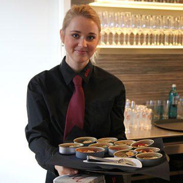 Kellnerin mit Speisen auf Tablett