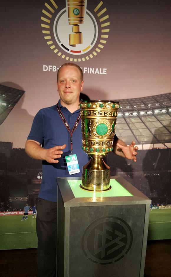 Benjamin Speidel, Fachbereichsleiter Küche in unserer Niederlassung Berlin-Messe-Potsdam, greift nach dem Pokal