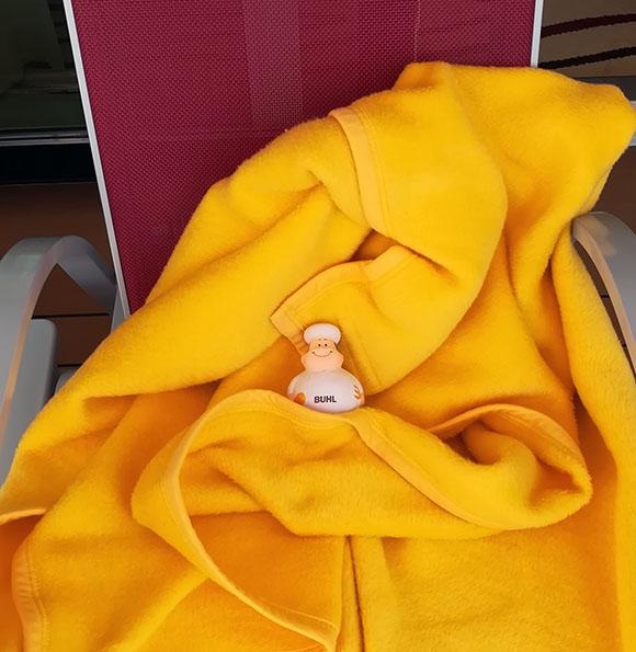 Bert kuschelt sich auf einem Bord-Liegestuhl in eine warme Decke
