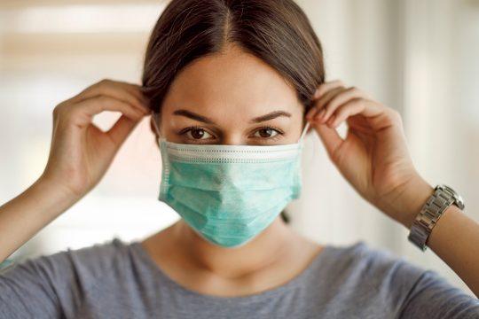 Frau zieht eine Schutzmaske an.