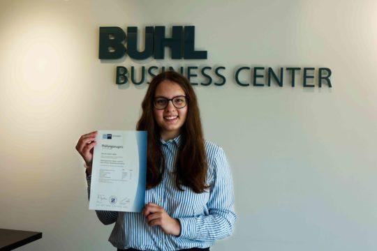 Hannah Späth zeigt voller Stolz ihr Prüfungszeugnis im Eingang des BUHL Business Centers